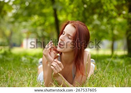 Beautiful Young Woman lying in Meadow - stock photo