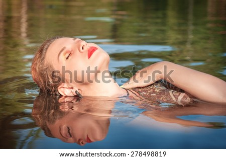 Beautiful young woman lying in the water outdoor - stock photo