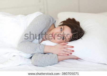 Beautiful young woman lying on a comfortable pillow, on white background