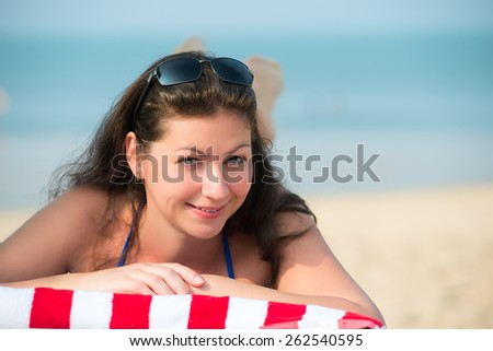 beautiful young woman lying on a lounger near the sea - stock photo