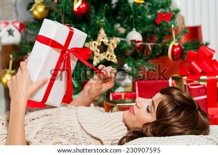 Beautiful young woman lying on carpet and opening Christmas present, Christmas presents - stock photo