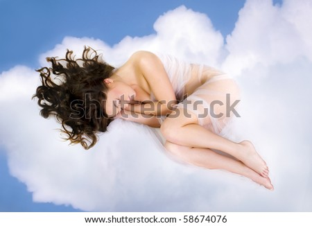 beautiful young woman lying on  clouds - stock photo