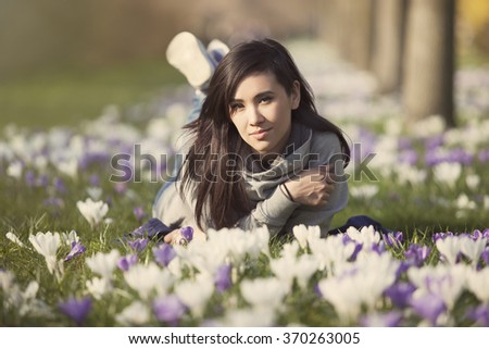 beautiful young woman lying on crocus lawn - stock photo