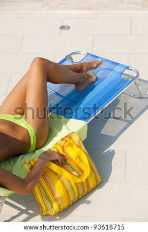 Beautiful young woman lying on deckchair by swimming-pool - stock photo