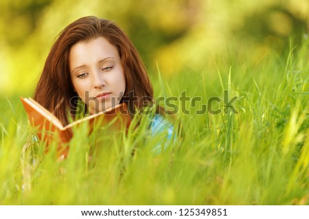 Beautiful young woman lying on grass and reading book, against background of summer green park. - stock photo