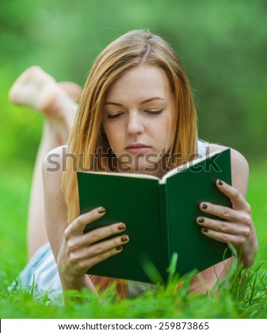 Beautiful young woman lying on grass and reading book, against green of summer park. - stock photo