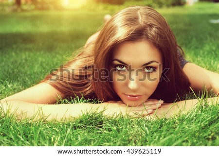 Beautiful young woman lying on grass in a park in a sunny summer day. - stock photo