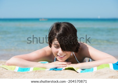 Beautiful young woman lying on her stomach on a towel sunbathing on a tropical beach with a calm ocean backdrop smiling with pleasure as she enjoys the hot summer sun - stock photo