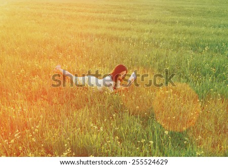 Beautiful young woman lying on summer meadow and reading a book. Image with sunlight effect - stock photo
