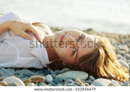 beautiful young woman lying on the beach and smiling - stock photo