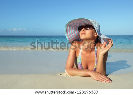 Beautiful young woman lying on the beach dreaming - stock photo