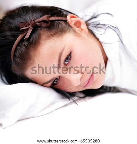 Beautiful young woman lying on the bed - stock photo