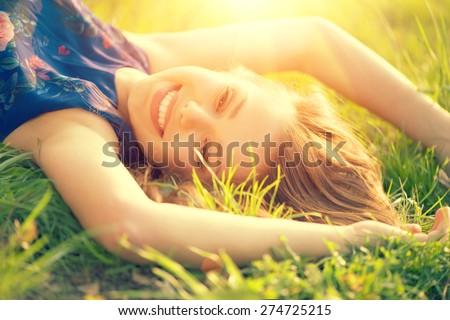Beautiful Young Woman lying on the field in green grass and laughing. Outdoors. Enjoy Nature. Healthy Smiling Girl on spring lawn - stock photo