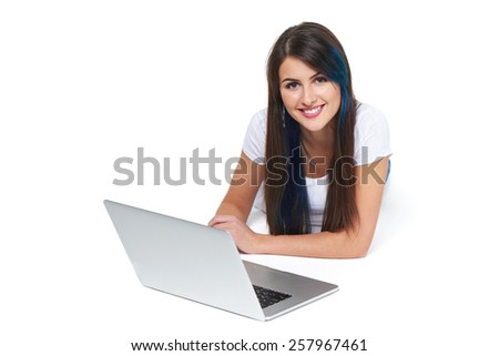 Beautiful young woman lying on the floor with laptop, isolated on white - stock photo