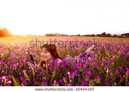 Beautiful young woman lying on the nature and talking at cellphone - stock photo