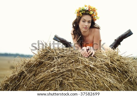 beautiful young woman lying on the round bale of hay on a field - stock photo