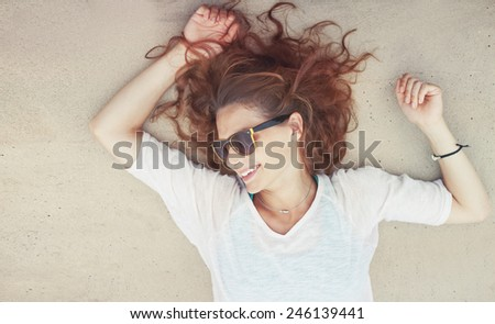 beautiful young woman lying on the sand with sunglasses, image with retro toning - stock photo