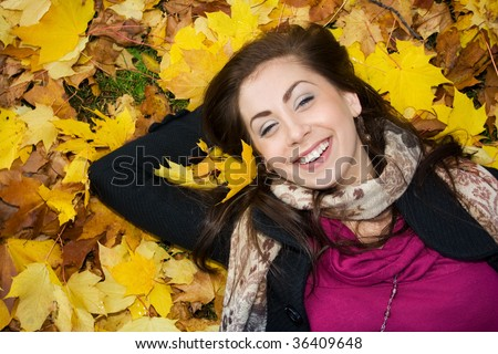 Beautiful young woman lying on the yellow leaves - stock photo