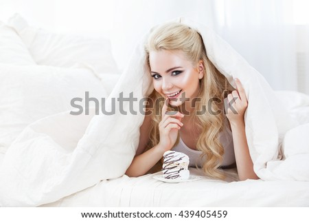 Beautiful young woman lying on white bed , covered head odiyalom and eat delicious cake . White hair color , shot in bright tone . Beauty girl face - stock photo