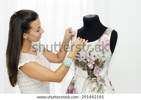 Beautiful young woman making a new dress on the on a tailoring mannequin. - stock photo