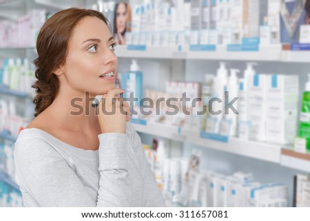 Beautiful young woman making decision in drugstore - stock photo