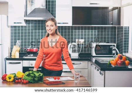 Beautiful young woman making healthy food standing happy smiling in kitchen preparing salad.  - stock photo