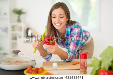 Beautiful young woman making healthy meal in the domestic kitchen. She is cutting red pepper on the kitchen board.