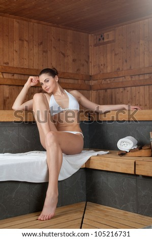Beautiful young woman making sauna in a spa center
