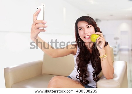 Beautiful young woman making selfie by her smart phone and smiling while sitting on the couch at home