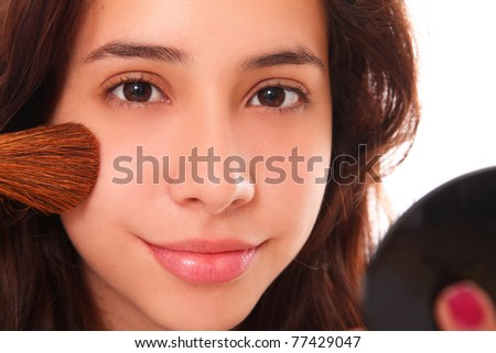 Beautiful young woman making up her face with a small smile on her lips - stock photo