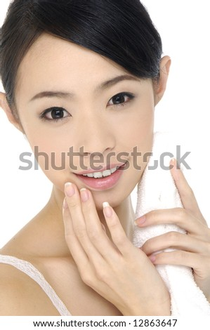 Beautiful young woman massaging her face - stock photo