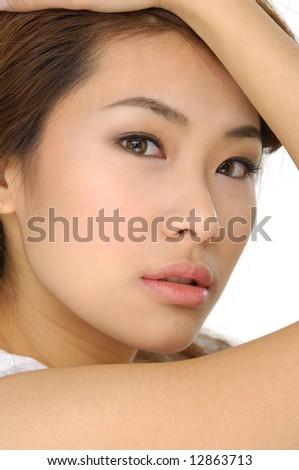 Beautiful young woman massaging her face - stock photo