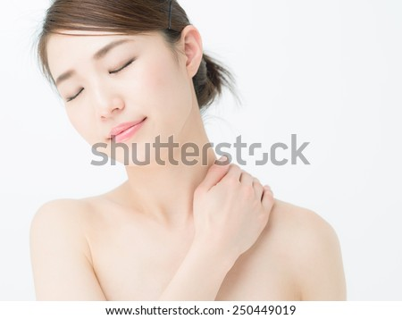 Beautiful young woman massaging her shoulder