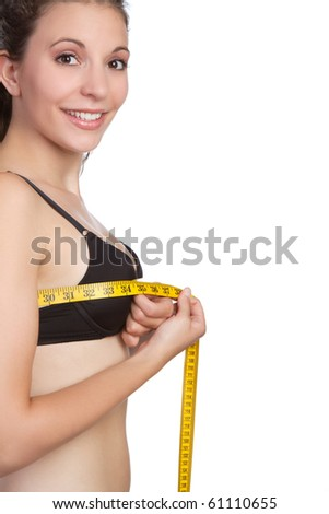 Beautiful young woman measuring bust - stock photo
