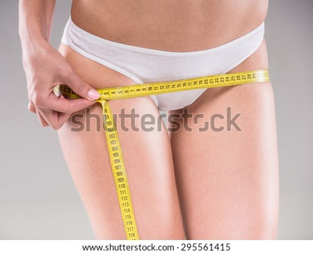 Beautiful young woman measuring her body with tape on gray background.