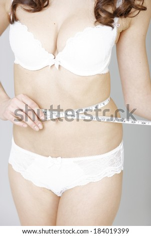Beautiful young woman measuring her waistline.