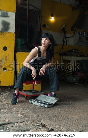 beautiful young woman mechanic holding tool near the box with tools for repairing cars in garage - stock photo