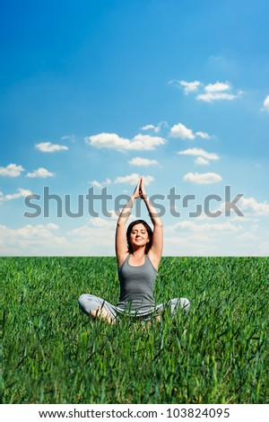 beautiful young woman meditating at the meadow at sunny day - stock photo
