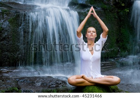 Beautiful young woman meditating in lotus position while doing yoga between waterfalls - stock photo