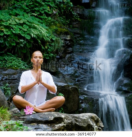 Beautiful young woman meditating in lotus position while doing yoga in a wonderful forest near waterfall - stock photo