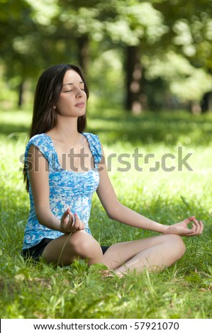 Beautiful young woman meditating in lotus position while doing yoga in the nature - stock photo