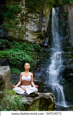 Beautiful young woman meditating in lotus position while doing yoga in the nature near waterfall - stock photo