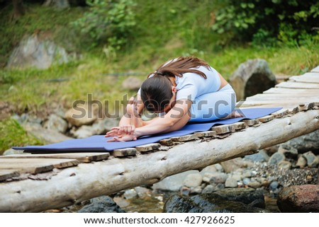 Beautiful young woman meditating in yoga pose at a mountain stream. Selective focus on woman.