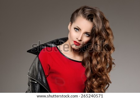 Beautiful young woman model brunette with long curled hair with red lips in leather jacket. Girl wave, curly hairstyle. Health hair shine. Beauty lady face with sexy glance. - stock photo