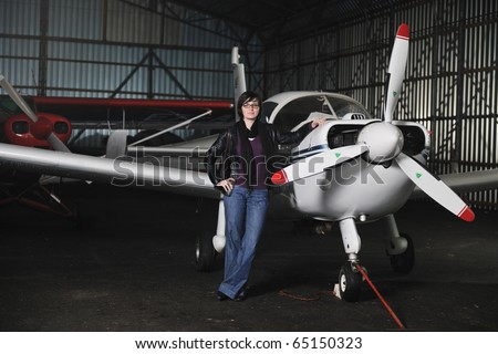 beautiful young woman model in fashion clothes posing in front of old private airplane - stock photo