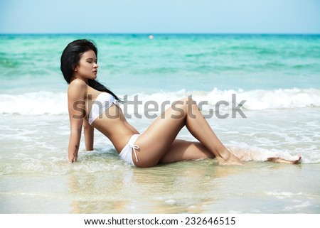 Beautiful young woman model in white bikini swim wear on a beach. Magic ocean and nature. Spa relax, vacation and resort. Travel to exotic countries  - stock photo