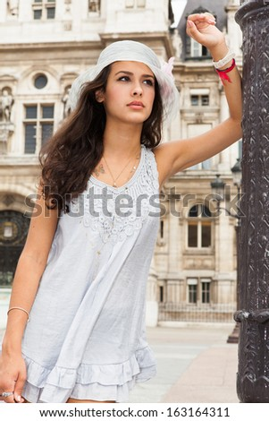 Beautiful young woman modeling in a historical plaza in Paris. - stock photo
