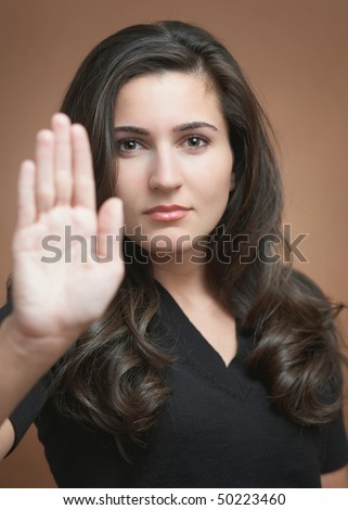 Beautiful young woman motioning to stop, focus on face - stock photo