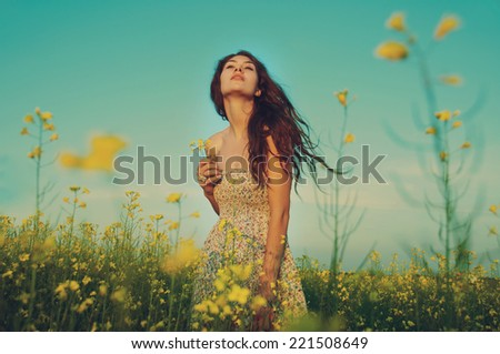 beautiful young woman moving and posing in the rapeseed field. retro toning effect  - stock photo