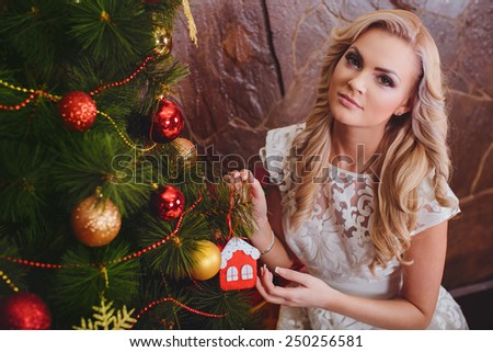 Beautiful young woman near a Christmas tree with gifts - stock photo
